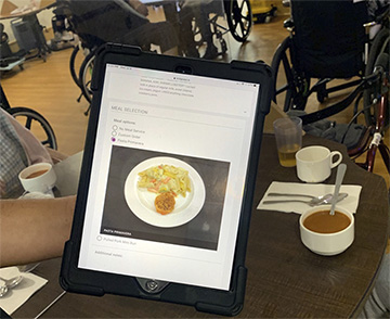 Residents are shown their meal options on a tablet. Staff input the meal choices at the table.